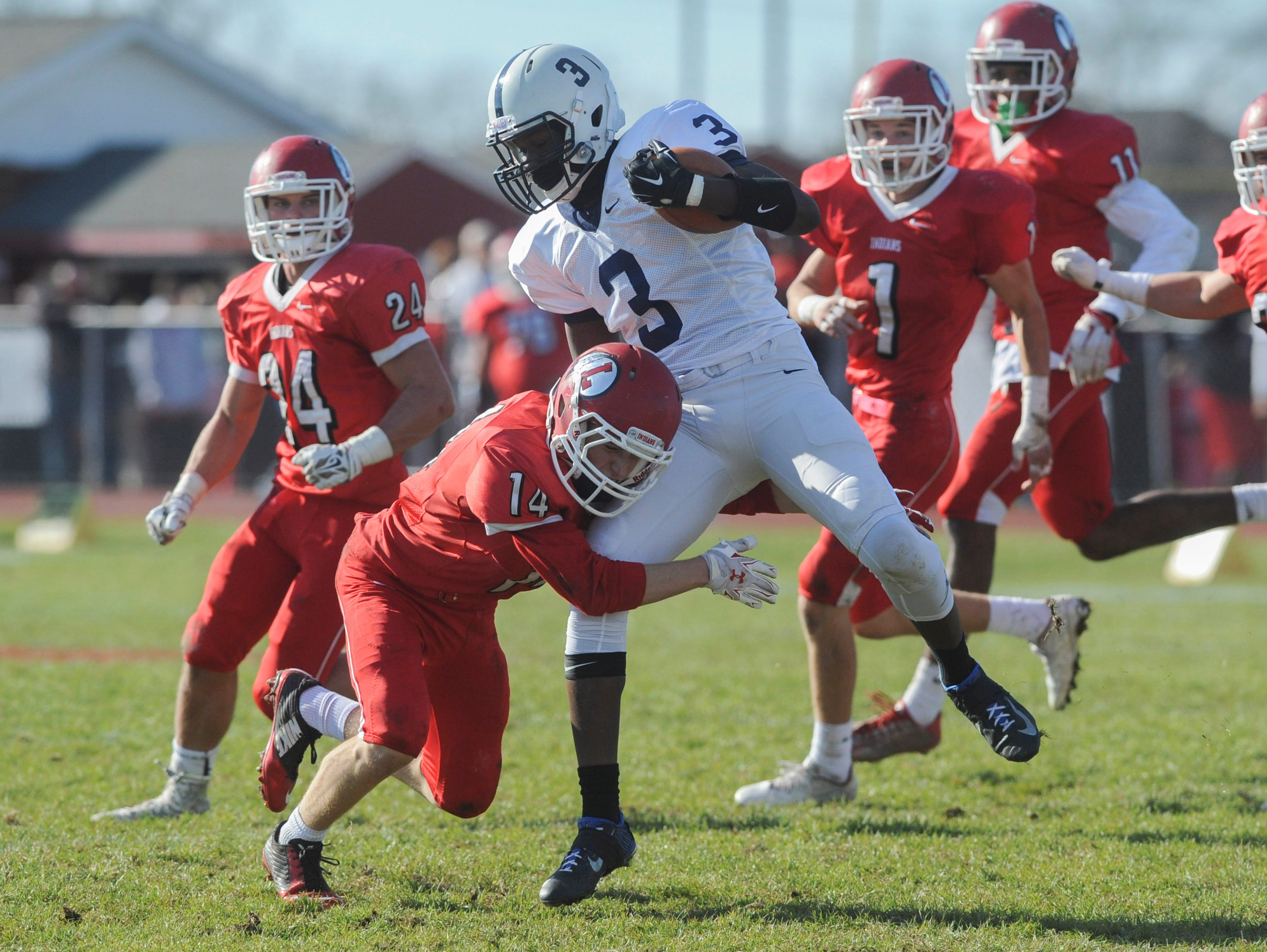 Lenape's Mike Doulong tackles Shawnee's Daevon Robinson during Thursday's Thanksgiving Day football game at Lenape. Thursday, November 26, 2015.