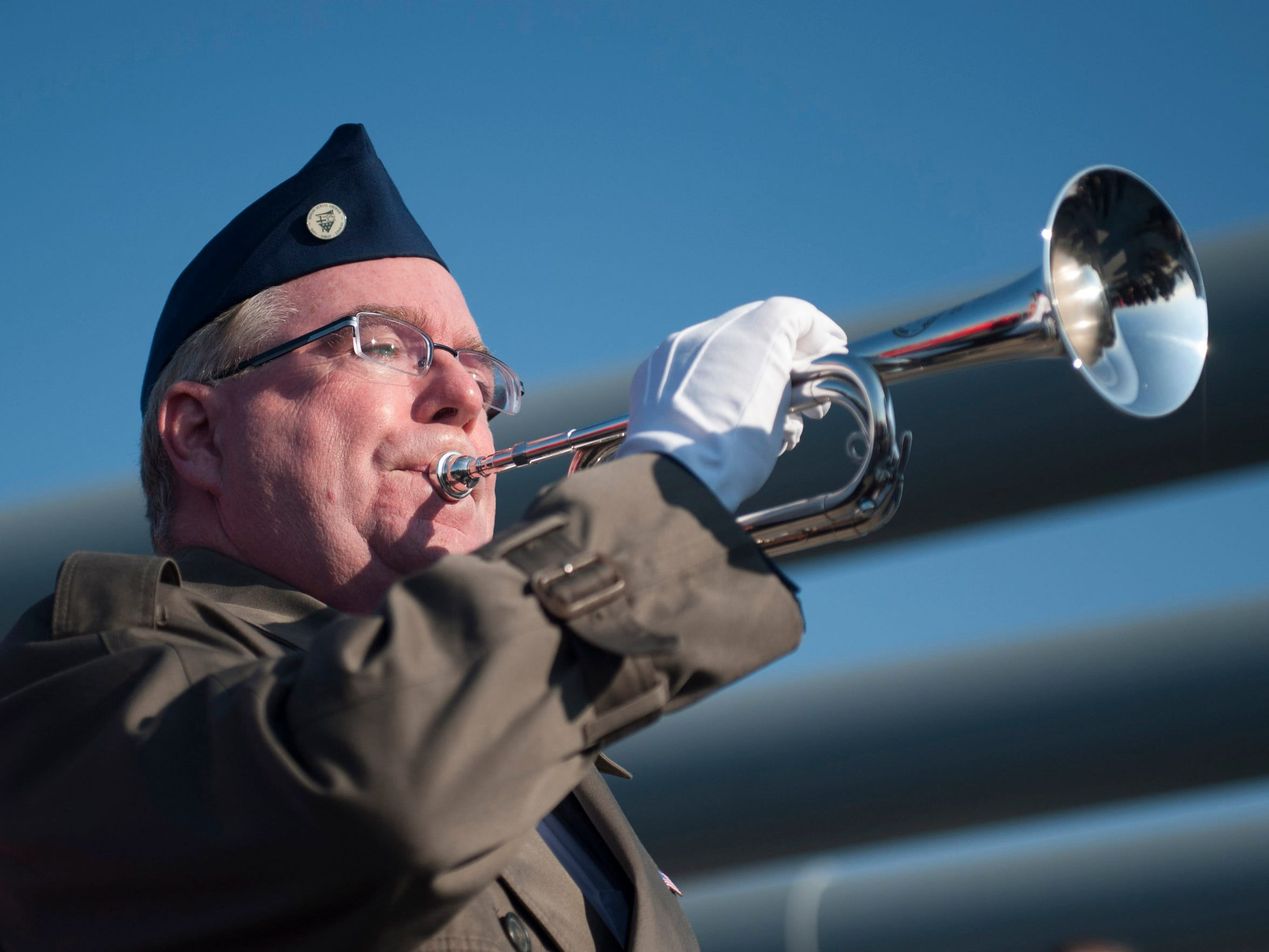 Bugler Greg Murphy plays Taps during the Pearl Harbor Day Commemoration aboard the Battleship New Jersey. Monday, December 7, 2015.