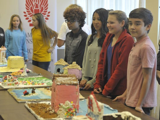 Julie Hill, Kaya Sathre-Nissley and Jordi Hull from the Scooby Doo Ginger Bread house team wait as viewers and judges take a look at the homes.