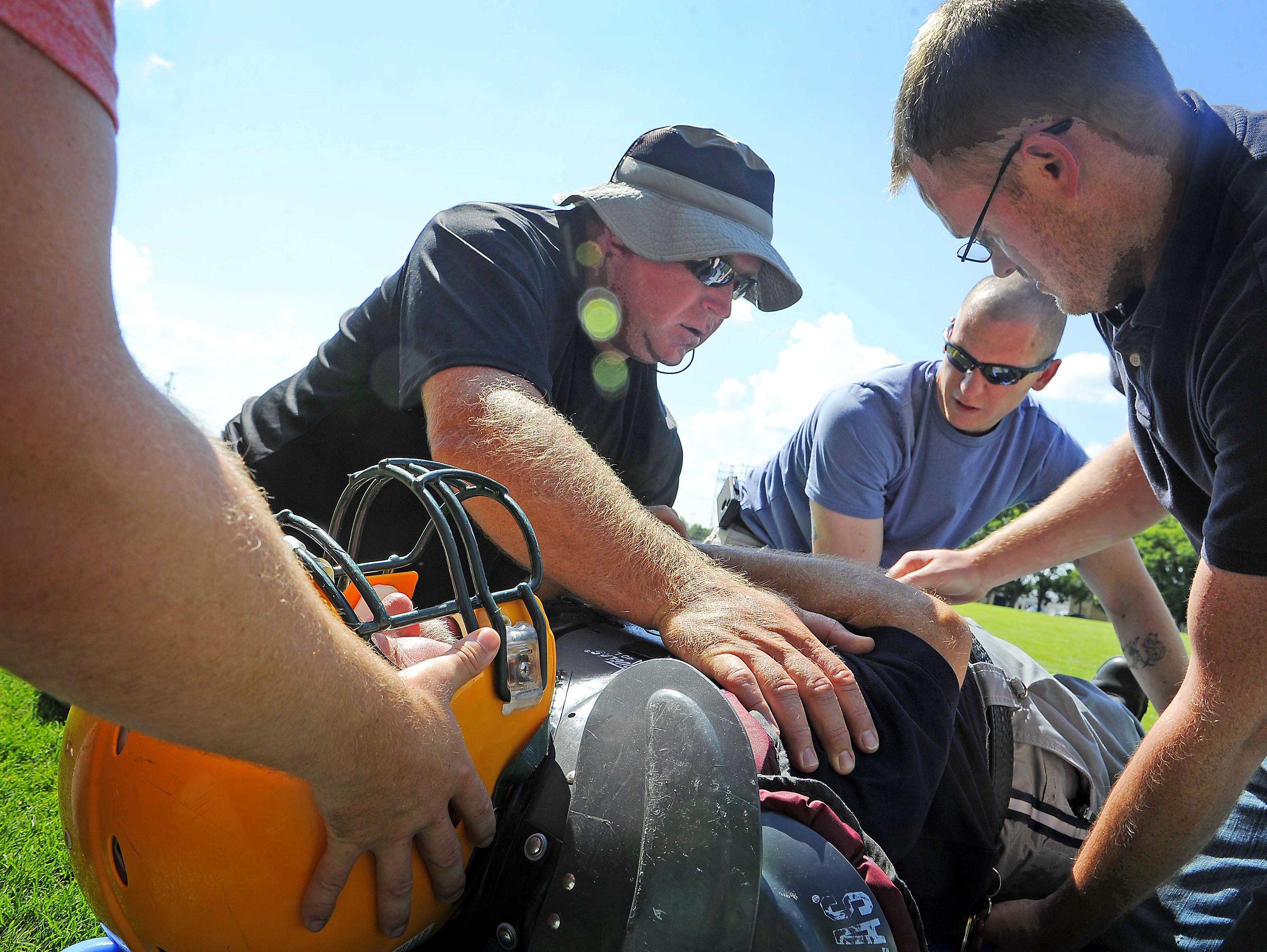 Brad Swope, Tyler Summers and Mark Burns practice putting an injured player (Scotty Blackburn) on a board to be transported. Sumner County emergency personnel and athletic trainers underwent training exercises in 2013.
