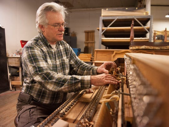 Bellmawr resident Kaz Bielicki restores a piano at Cunningham Piano Company in Philadelphia.