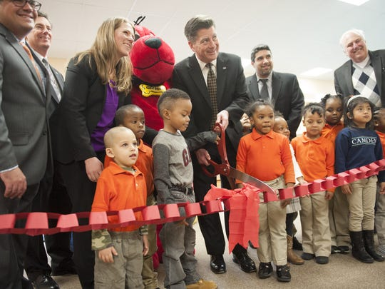 Jim Cawley (center), President and CEO of United Way of Greater Philadelphia and Southern NJ, cuts the ribbon on the region's first Club Connect Reading Oasis at Riletta Twyne Cream School in Camden with the help of students.