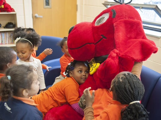 Clifford the Big Red Dog gets a hug from pre-K student Arriana Branch Friday as the United Way of Greater Philadelphia and Southern NJ began the region's first Club Connect Reading Oasis at Riletta Twyne Cream School in Camden.