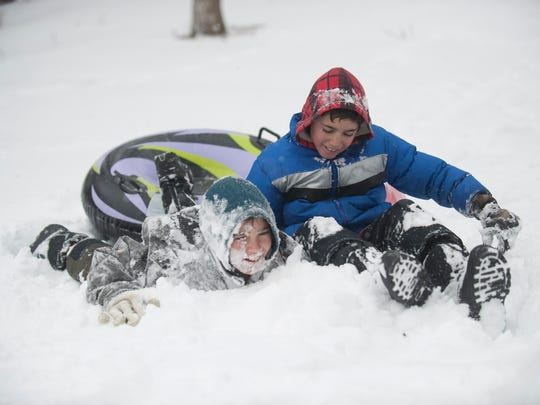 Ricky (left) and Eric Henderson of Mount Ephraim collide Saturday as they sled at Nutcracker Hill in Audubon as a winter storm makes its way through the region.