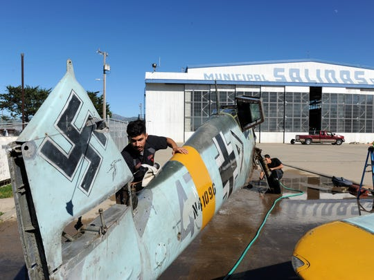 Abraham Garcia washes down the fuselage of a World War II-era German Messerschmitt BF-109 at Airmotive's hangar at Salinas Municipal Airport on Monday.