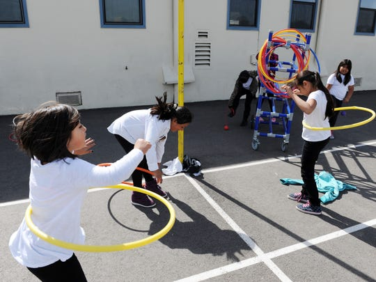 Girls practice hula hoop and other coordination activities