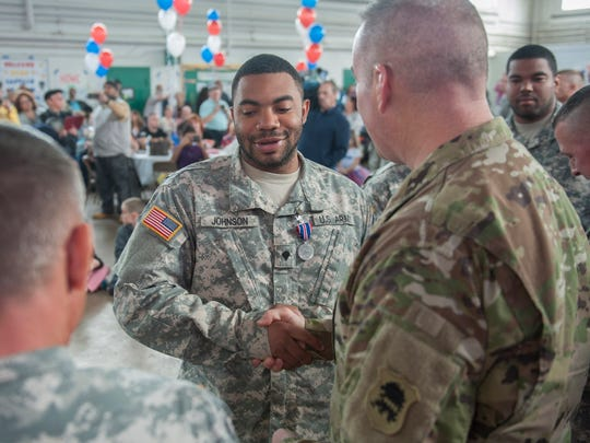 SPC Brian Johnson of Willingboro receives his Distinguished Service medal from Col. Edward Chrystal during the welcome home celebration for 328th Military Police Company, New Jersey Army National Guard. More than 120 Citizen-Soldiers of the 328th Military Police Company, New Jersey Army National Guard, were Welcomed Home by senior military leadership, friends and family at the National Guard Armory in Cherry Hill after a nearly yearlong mobilization to Guantanamo Bay, Cuba. Wednesday, March 16, 2016.