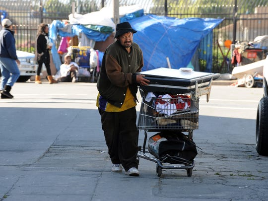 A Chinatown resident moves what possessions he can during a sweep by the city of Salinas of homeless encampments in the Market Way area.