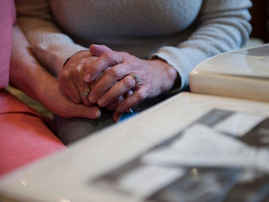 Beth Harley holds the hand of her mother, Janet String, 79, as she visits with her at the Brandywine Senior Living facility in Voorhees. Photographs can help families recall happy memories to ease the transition of downsizing.