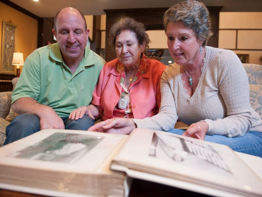 Beth Harley and Tom String look through old pictures as they visit with their mother, Janet String, 79, at the Brandywine Senior Living facility in Voorhees.