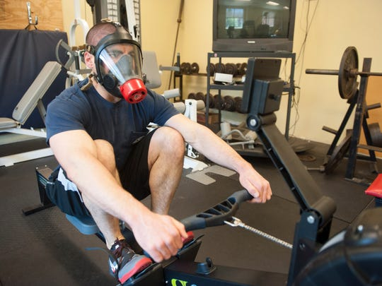 Cherry Hill Firefighter Jim Keegan works out on the rowing machine while wearing an oxygen deprivation mask. Wednesday, April 6, 2016.