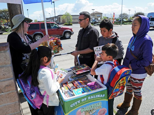 """As Kelly Henderson and Luis Alejandre from the library man the """"Palatero Program"""" cart, Areli Vargas, 8, Jovanni Cazares, 10, and his brother Omar, 5, discover new reading material."""