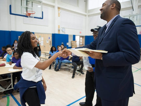 Assemblyman Arthur Barclay hands an award to Unique Alford as he awards the girls' and boys' basketball teams and cheerleading team at KIPP Cooper Norcross Academy prior to a pizza party Friday.