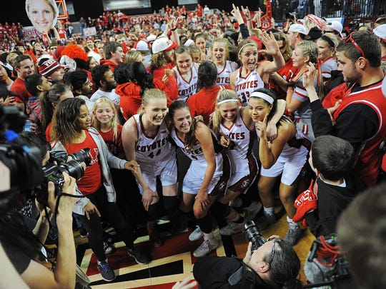 USD players pose for a photograph while celebrating their 71-65 win over Florida Golf Coast with their fans after the WNIT Championship game against Florida Golf Coast Saturday, April 2, 2016, at the DakotaDome in Vermillion, S.D.