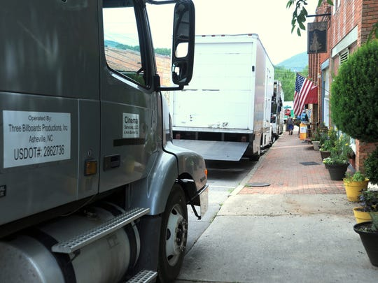 Trucks carrying production equipment line Cherry Street as crews convert the Town Pump Tavern to a movie set.