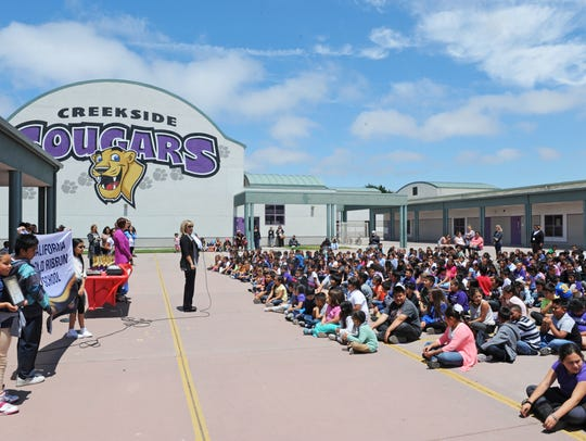 Principal Marilyn Cline addresses an outdoor assembly