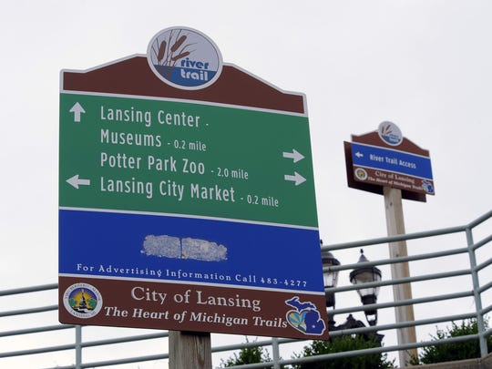 A sign near the Lansing Center gives distances and directions for walkers, runners and bicyclists in Lansing  on the River Trail .