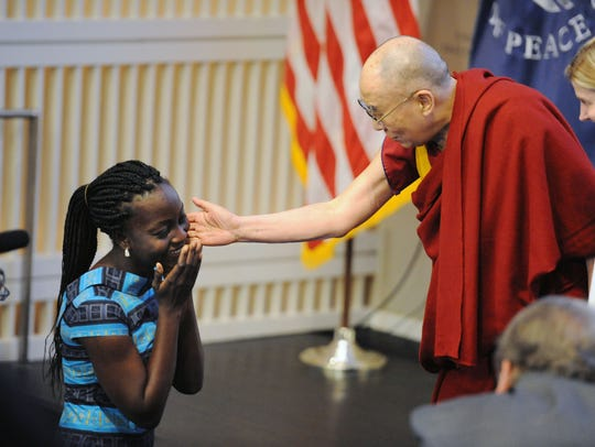 The Dalai Lama reaches out his hand to greet Victoria