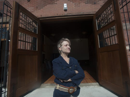 Cassie MacDonald stands at the front doors of Camden's new center for the arts, Camden FireWorks, a historic firehouse in the Waterfront South community.