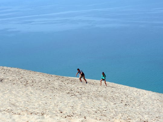 Jake and Kaitlyn Rembold of Ohio climb an area of the dunes on the Pierce Stocking Scenic Drive.