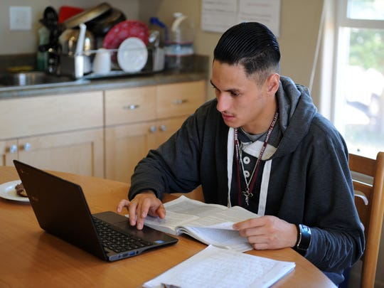 Seen here in the kitchen of his Rancho Cielo transitional housing, Luis Corona works on assignments for classes he is taking at Hartnell College.