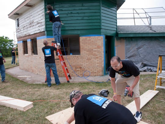 GM volunteer Carlos Cuellar, lower right, helps renovate the baseball field at Westside Park on Tuesday, June 28, 2016 in Lansing for the GM Field Makeover. The Lansing Lugnuts and General Motors Lansing Regional Manufacturing plants partnered for the third GM Field Makeover.