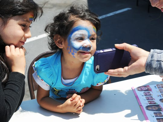 Milagros Lopez, 2, checks out her face paint with a phone camera at the festival.