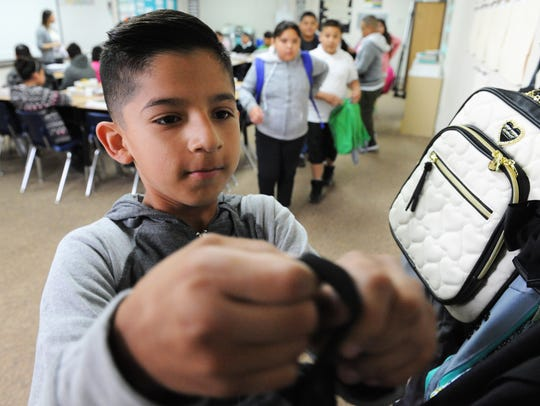 Kid file in row by row to hang up their backpacks at