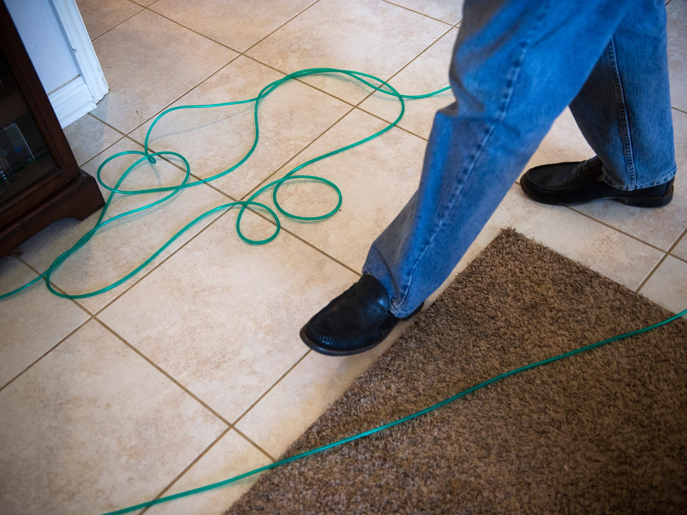 John Morton, of Evansville, walks carefully around a hose connected to an oxygen tank in his home, Thursday, Aug. 25, 2016. John and his wife, Carole, have been living with alpha-1 antitrypsin deficiency, a genetic disorder that can lead to lung and liver diseases.