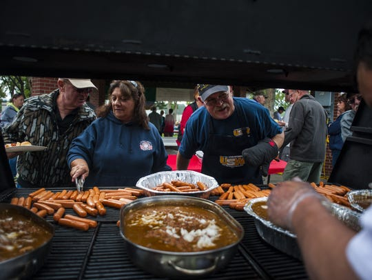 Tina Ball, left, and Fred Janicke, right, cook hotdogs