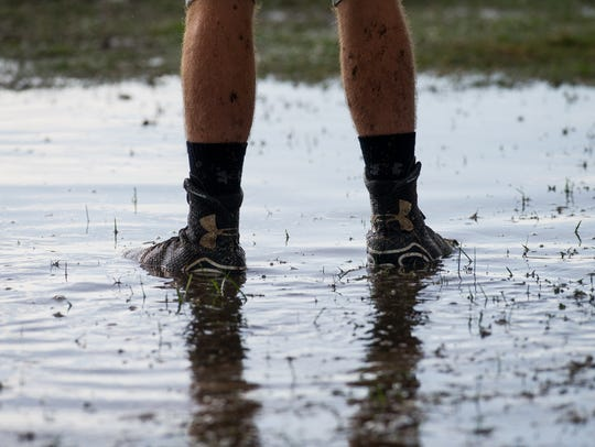 Ave Maria football players stand in the mud on their