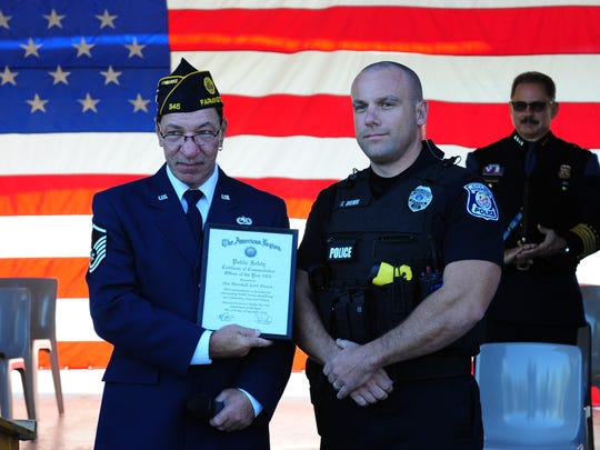 American Legion #346 Commander Dale Baxter presents Farmington Police Officer Scott Brown his plaque as he is named Officer of Year for the city of Farmington.