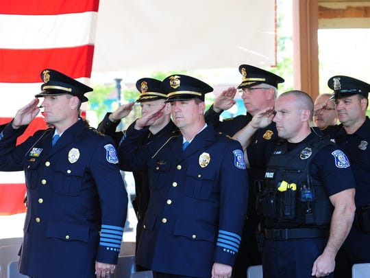 Farmington and Farmington Hills officers salute during the singing of the Star Spangled Banner.