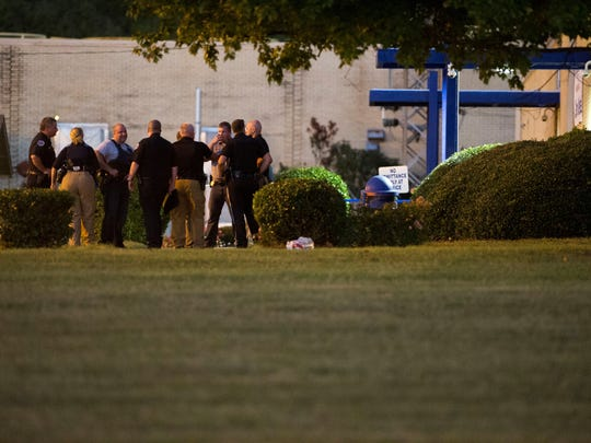 Officials stand outside Thomas & Betts Corp., where a shooting took place Thursday that left three dead in Athens, Tenn.