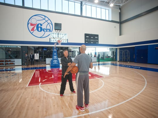 Sixers coach Brett Brown (left) chats on the court