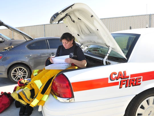 CAL FIRE Assistant Chief Julia Honer sits in her trunk doing paperwork in 2011.