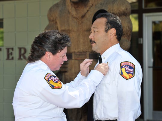 CAL FIRE Assistant Chief Julia Honer pins the new Battalion Chief badge onto Don Tashima in 2011.