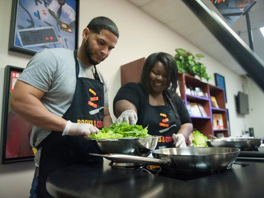 (From left) Jose Rodriguez and Mikala Allen cook during a cooking/nutrition class in Camden with a new mobile kitchen, part of the Camden County Library System's newest initiative on food literacy.