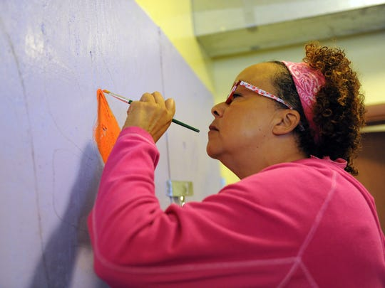 After carefully sketching out a huge butterfly, volunteer Sharon Jayubo begins to paint it.