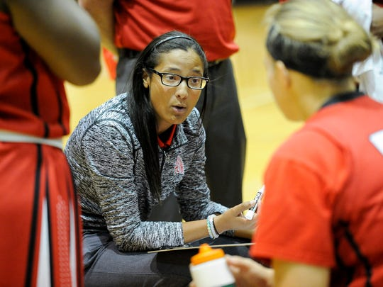 First year Harrison girls basketball coach Kiara Butler speaks with the team during a time out during their game against North at North High School in Evansville, Tuesday, Nov. 1, 2016.
