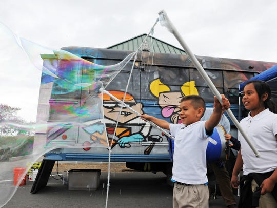 Alisal Community School second-graders line up to make gigantic bubbles outside the Physics Bus.