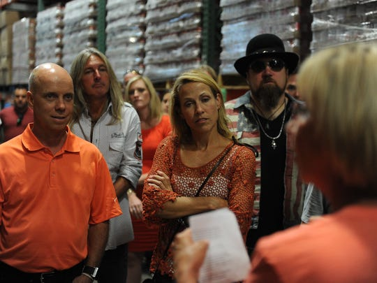 Stars including Scott Hamilton, left, 50 Cent and Sheryl Crow prepare to stuff bags with carrots and apples at Second Harvest Food Bank on Sept. 9, 2014, in Nashville. Director Jaynee Day, right, gives instructions.