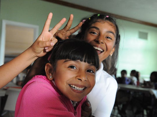 Wiith some help, Andrea Lopez, 9, puts rabbit ears on her sister Noemi, 6, at the L.I.F.E. after-school program in east Salinas.