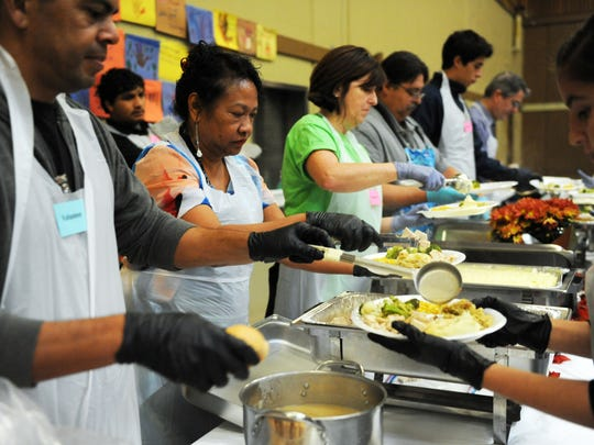 Volunteers help fill plates held by table servers at the Castroville Community Feast on Thanksgiving Day.