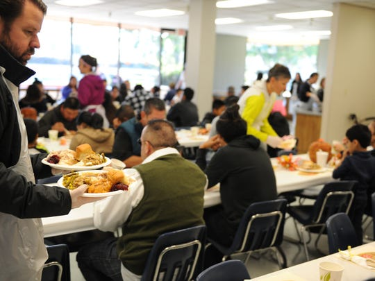 In this file photo, a volunteer serves plates on Thanksgiving at the Salvation Army in Salinas.