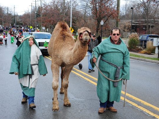 Members of Christ Lutheran Church walk with a camel in the parade.