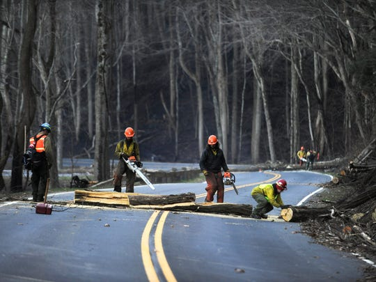 Dec 2, 2016; Gatlinburg, TN, USA; A U.S. Forest Service crew from the Helena National Forest remove fallen trees from Newfound Gap Road in the Great Smoky Mountains National Park. They are part of the 458 personnel deployed to fight the Chimney Tops 2 fire that has killed 13 people and destroyed more than 700 structures. Mandatory Credit: Paul Efird/Knoxville News Sentinel via USA TODAY NETWORK