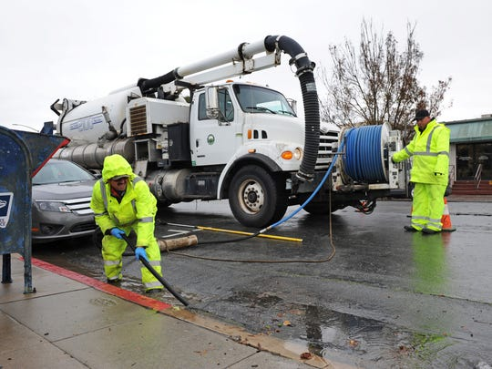 City workers unplug a storm drain on Thursday morning on W. Gabilan Street in Salinas. Rain and gusty winds brought down many leaves, blocking outlets.
