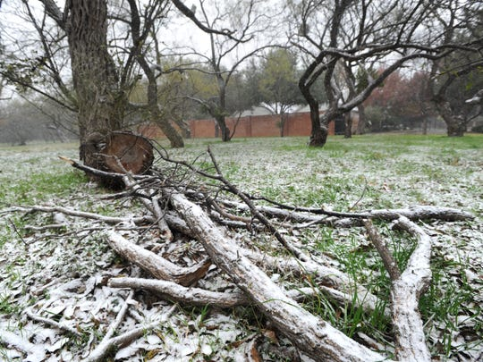 A sprinkling of snow covers logs in south Abilene on Thursday.