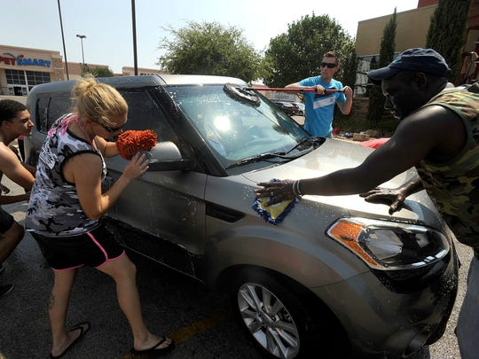 Members of the Dyess We Care Team wash cars in the Shops of Abilene parking lot during a fundraiser for The Mission church's Mobile Salon in 2015.